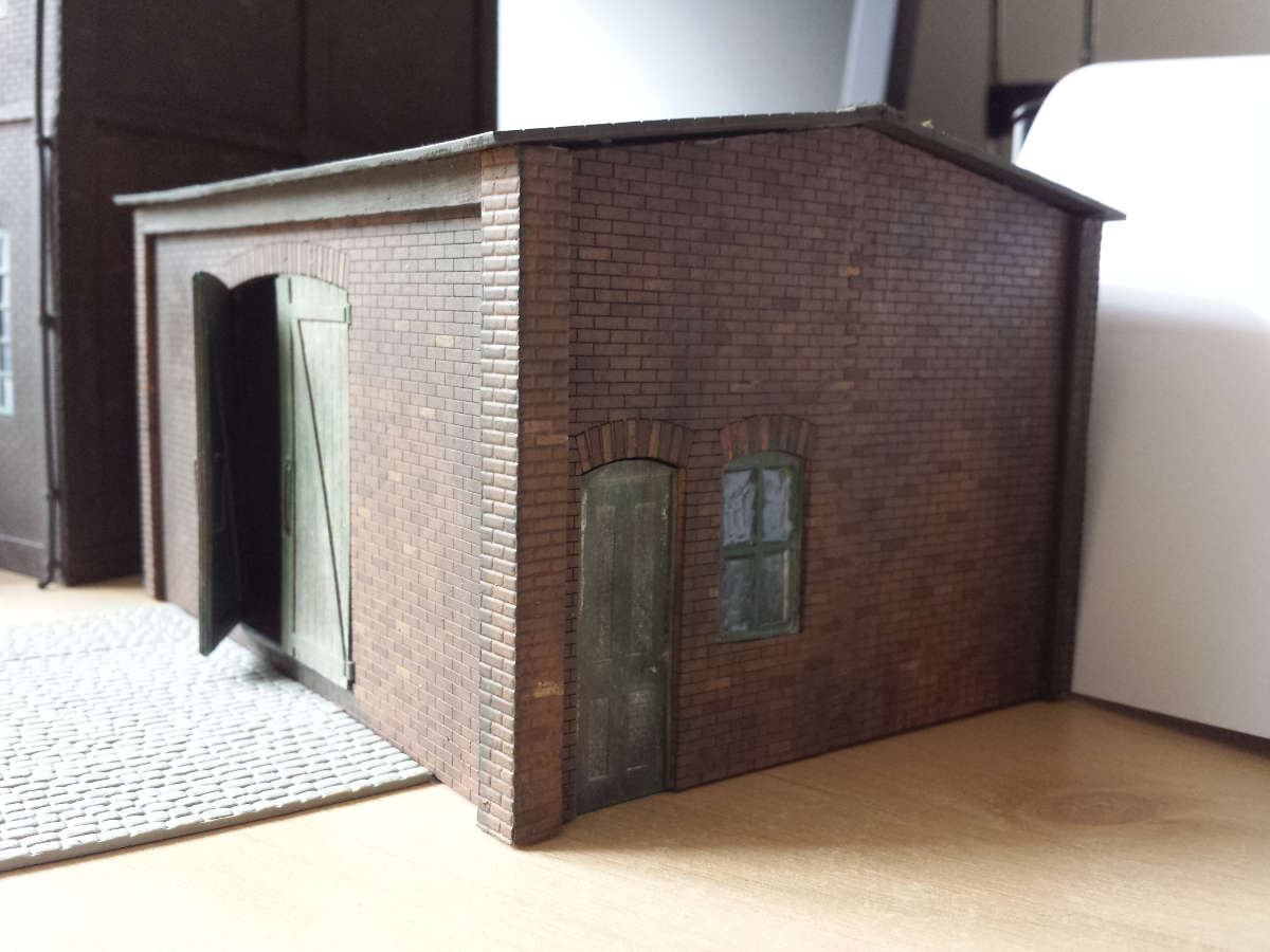 "An exceptionally well finished goods shed in O gauge by Steve Farrands. Comment from Steve: ""The main building was constructed as a full relief building. I did not use the upper floor opening, which I adapted into making a vehicle workshop to go at the side of the warehouse. I had pictures of a particular warehouse I wanted to model and using colour photographs of the actual building I made the main unit. The windows were adapted by cutting out the middle frame and once glazed the open part was added to the main frame. The glazing was ordinary wood glue dragged across the panes using a cocktail stick. Some panes had dried broken but I think they look very realistic for broken panes of glass. I added guttering and downpipes as well."" Submitted by Steve Farrands on 8th September 2016"