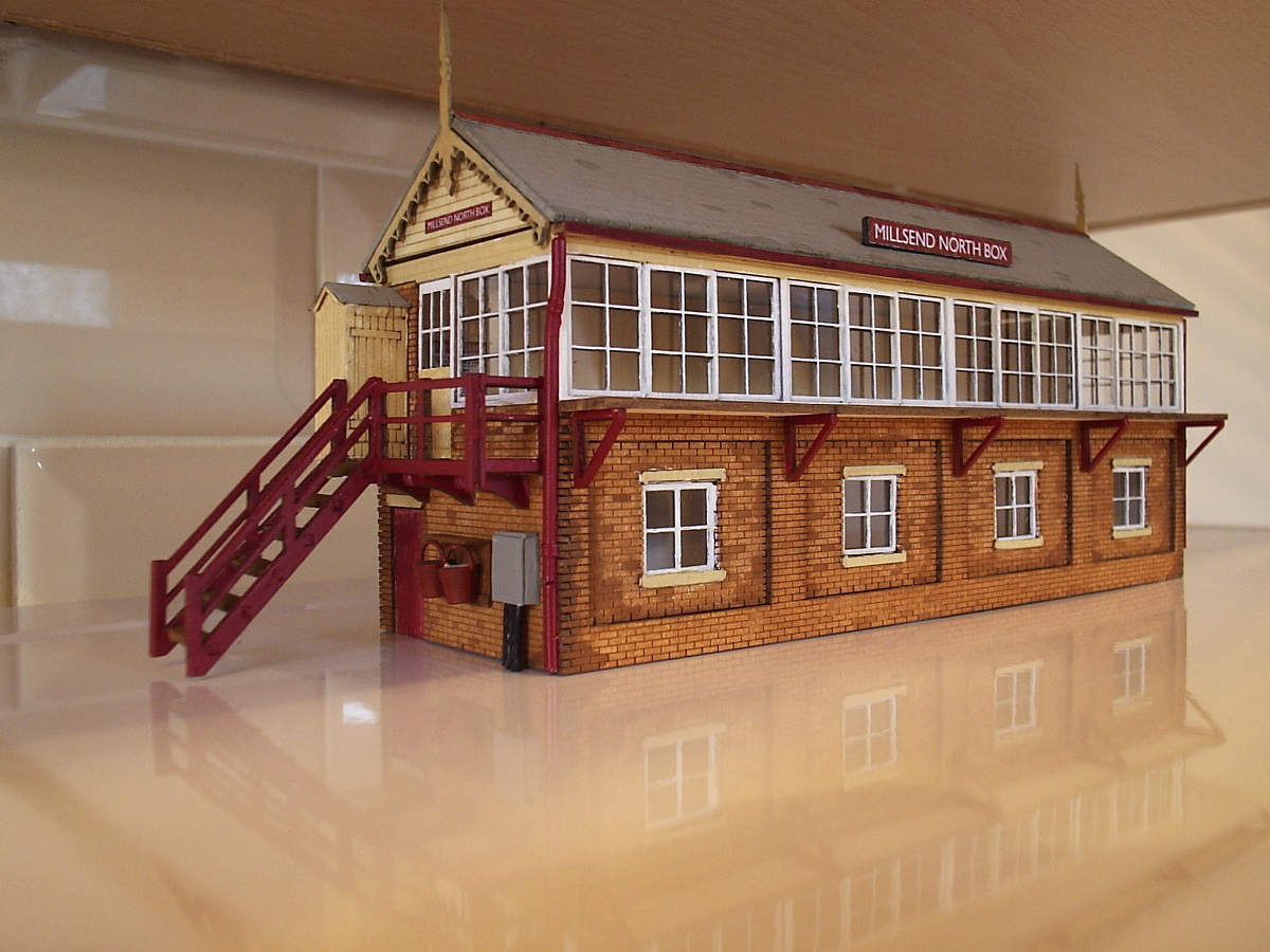 "Large signal box kit built by Jim Dobson of Fleetwood for his ""Millsend layout"".  Painted with thinned enamel paint. Additions to the kit plastic drain pipes, gutters made from sprue left over from the kit, water buckets, power box and name boards. Submitted by Jim Dobson on 29th February 2016"